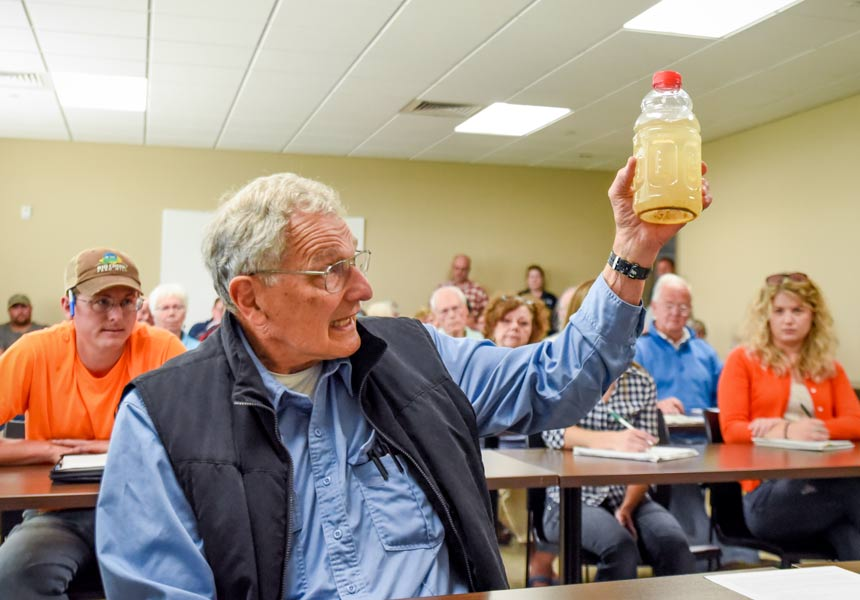 William Faller holds up a water sample from a local creek containing an overabundance of silt, bacteria and nutrients during a water quality hearing in Kewaunee County on June 27. (Photo by Mike Peters)