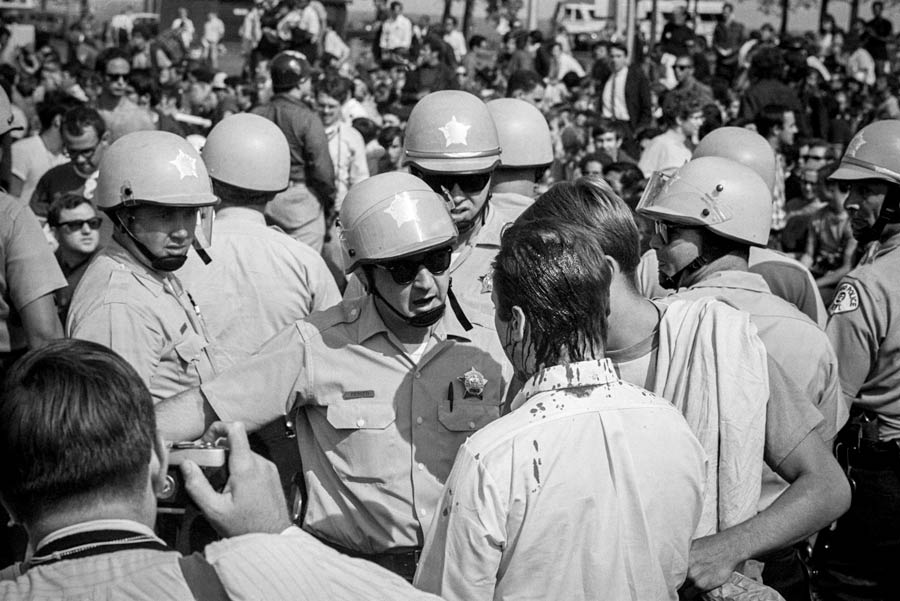 Helmeted Police Confront An Anti War Protester Bleeding From The Top Of His Head Onto Neck And Shirt At 1968 DNC Protests Bettman Getty Images
